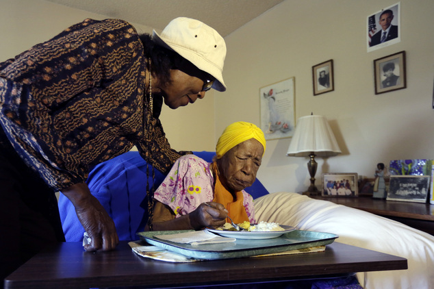 FILE - In this Monday, June 22, 2015 photo, Lois Judge, left, helps her aunt Susannah Mushatt Jones, during breakfast in Jones' room at the Vandalia Avenue Houses, in the Brooklyn borough of New York.<div class='article-ad'><script src=