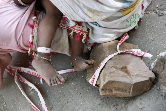 Sarta Kalara feeds her 15-month-old Shivani as one end of a barrier tape is tied to Shivani's foot and the other end to a stone to prevent Shivani from running away, when she works at a construction site nearby, in Ahmedabad, India, April 19, 2016. REUTERS/Amit Dave