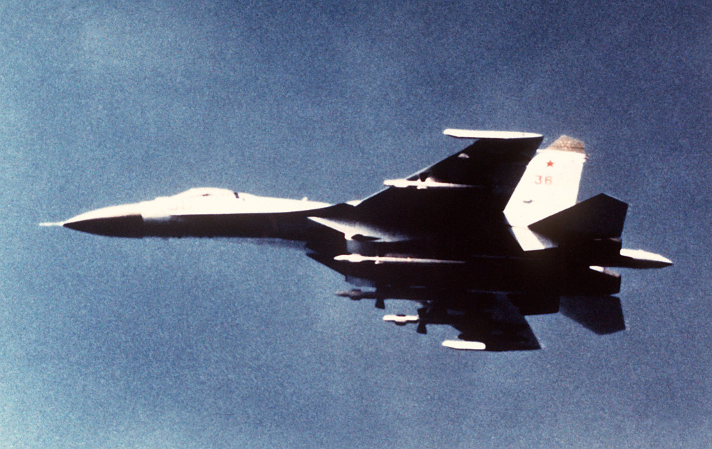 An air-to-air left side view of a Soviet SU-27 Flanker aircraft.