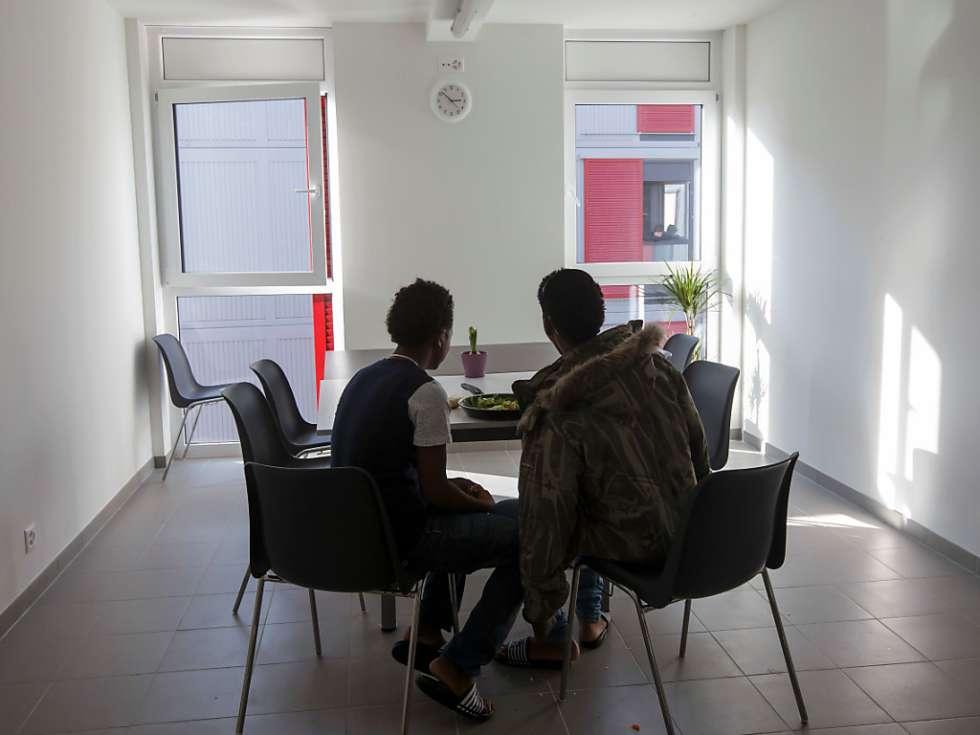 Zwei-Fluechtlinge-essen-in-einem-Zentrum-fuer-junge-Asylsuchende-in-Genf-Symbolbild-