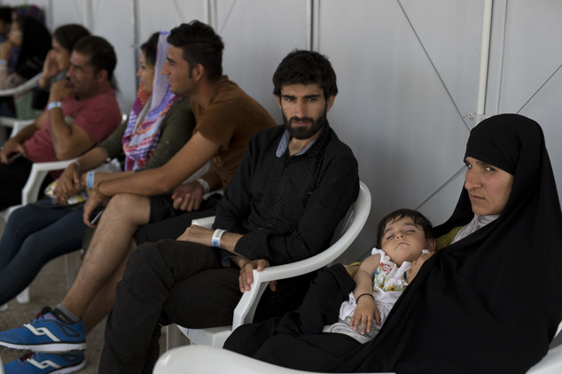 Afghan migrants who live in the Hellenikon refugee and migrant camp of Athens register for asylum on Monday, June 13, 2016. Authorities began registering applications at the site Monday, in a processes expected to last months as more than 50,000 migrants and refugees have been stranded in Greece in the wake of European border closures. (AP Photo/Petros Giannakouris)