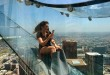 """Angela Cox a reporter with Seven Network Australia takes a photo with her phone as she takes ride down a glass slide during a media preview day at the U.S. Bank Tower building in downtown Los Angeles on Thursday, June 23, 2016. Starting this weekend, thrill-seekers can begin taking the """"Skyslide"""" a 1,000 feet high and perched on the outside of the tallest skyscraper west of the Mississippi. All that separates riders from the dizzying space below is a piece of glass just 1 1/4 inches thick. (AP Photo/Richard Vogel)"""