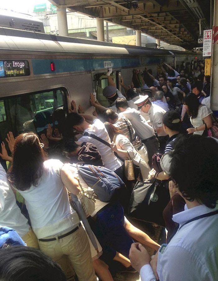 Emberek együtt dolgoznak, hogy segítsenek kiszabadítani valakit, aki beszorult a vonat és a peron közé.