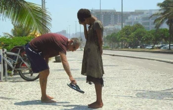 Egy férfi odaadja a cipőjét egy hajléktalan lánynak Rióban.