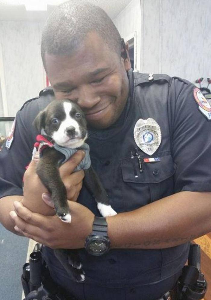 Egy rendőr ölelgeti új családtagját.
