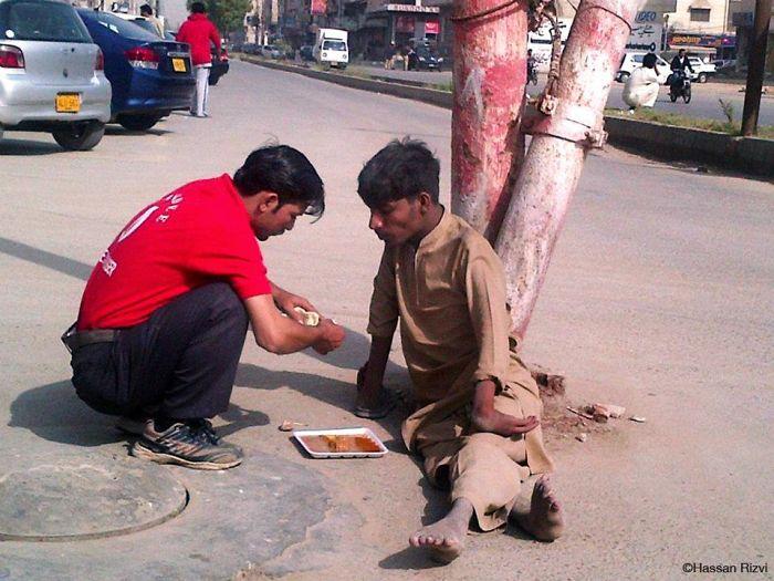 Egy pakisztáni pincér megetet egy hajléktalant, aki nem tudja használni a kezét.