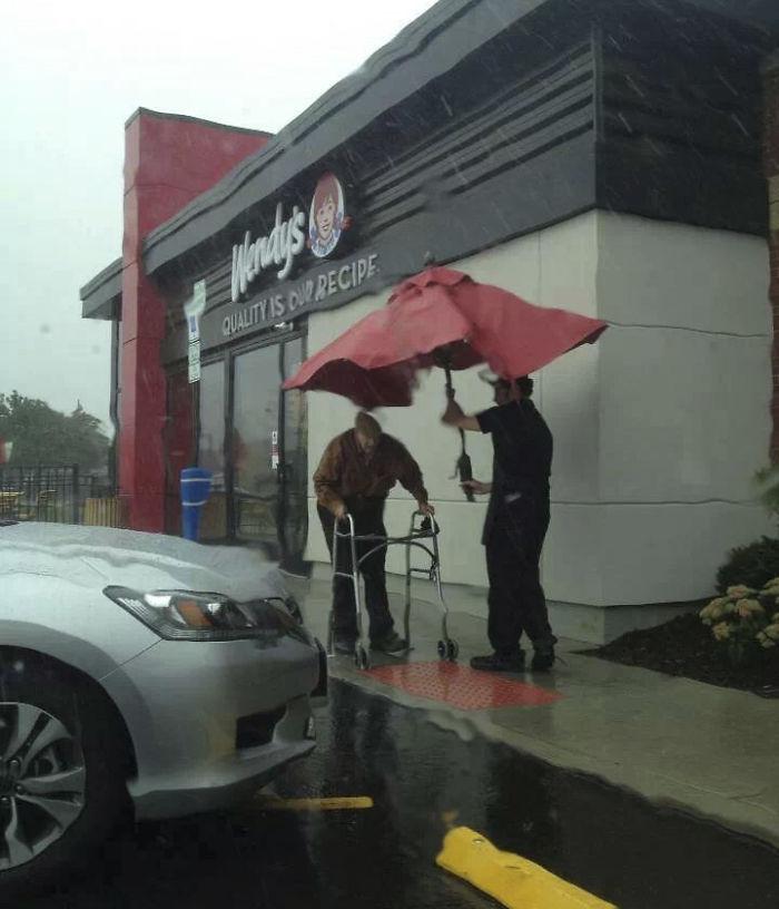 Egy gyorsétterem alkalmazottja a helyi napernyővel kísérte ki az idős bácsit az autójához.