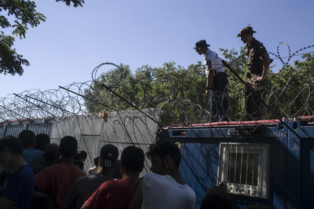 Hungarian police and army officers oversee the distribution of food as people queue inside a migrant camp at Serbia's border with Hungary, in Horgos, Serbia, Monday, July 11, 2016. In what appears to be another refugee crisis in the making in Europe, the numbers are surging at camps on Serbia's border with EU country Hungary. The numbers have been growing since last week, when Hungary introduced forced deportations of migrants caught within 8 kilometers (5 miles) of border fences. (AP Photo/Marko Drobnjakovic)