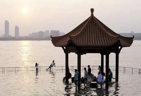 tourists-take-pictures-near-a-pavilion-flooded-by-the-swollen-yangtze-river-in-wuhan-hubei-province-june-19-2015-picture-taken-june-19-2015-reuterschina-daily