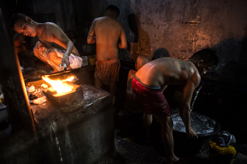 An inmate cooks his dinner as other detainees take a bath inside the Quezon City jail at night in Manila in this picture taken on July 21, 2016. There are 3,800 inmates at the jail, which was built six decades ago to house 800, and they engage in a relentless contest for space. Men take turns to sleep on the cracked cement floor of an open-air basketball court, the steps of staircases, underneath beds and hammocks made out of old blankets. / AFP PHOTO / NOEL CELIS / TO GO WITH AFP STORY: Philippines-politics-crime-jails, FOCUS by Ayee Macaraig