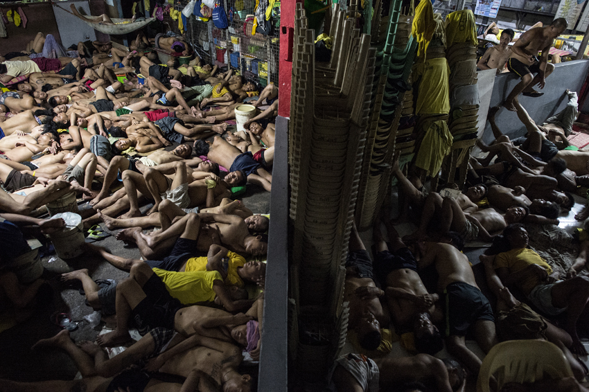 Inmates sleep on the ground inside the Quezon City jail at night in Manila in this picture taken on July 21, 2016. There are 3,800 inmates at the jail, which was built six decades ago to house 800, and they engage in a relentless contest for space. Men take turns to sleep on the cracked cement floor of an open-air basketball court, the steps of staircases, underneath beds and hammocks made out of old blankets. / AFP PHOTO / NOEL CELIS / TO GO WITH AFP STORY: Philippines-politics-crime-jails, FOCUS by Ayee Macaraig