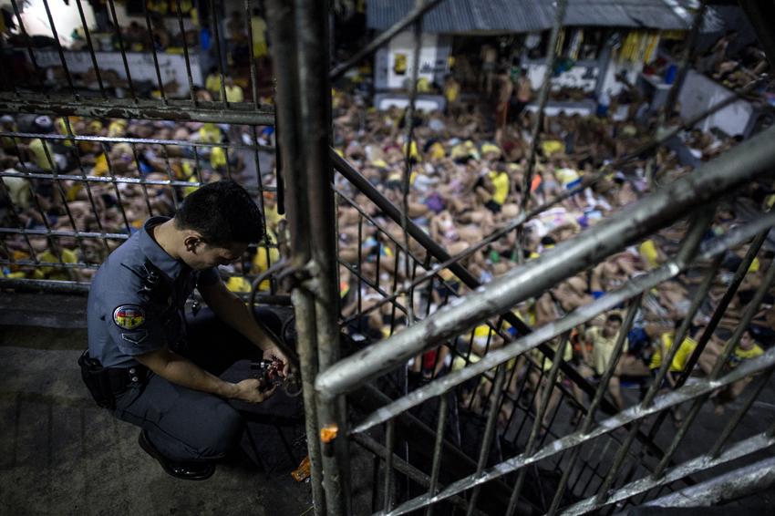 A prison guard locks a gate inside the Quezon City jail at night in Manila in this picture taken on July 21, 2016. There are 3,800 inmates at the jail, which was built six decades ago to house 800, and they engage in a relentless contest for space. Men take turns to sleep on the cracked cement floor of an open-air basketball court, the steps of staircases, underneath beds and hammocks made out of old blankets. / AFP PHOTO / NOEL CELIS / TO GO WITH AFP STORY: Philippines-politics-crime-jails, FOCUS by Ayee Macaraig