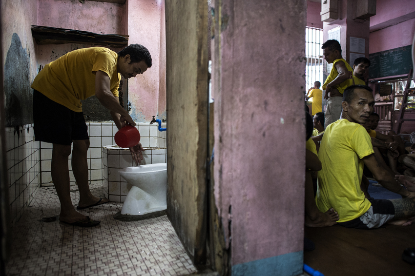 An inmate cleans the toilet at the Quezon City Jail in Manila in this picture taken on July 29, 2016. There are 3,800 inmates at the jail, which was built six decades ago to house 800, and they engage in a relentless contest for space. Men take turns to sleep on the cracked cement floor of an open-air basketball court, the steps of staircases, underneath beds and hammocks made out of old blankets. / AFP PHOTO / NOEL CELIS / TO GO WITH AFP STORY: Philippines-politics-crime-jails, FOCUS by Ayee Macaraig