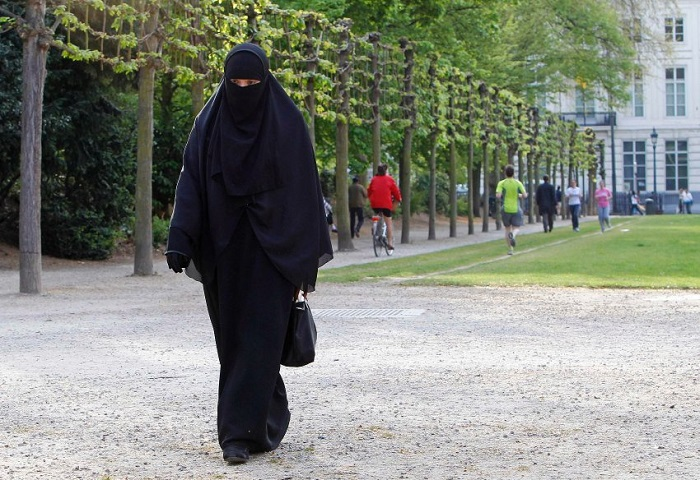 Salma, a 22-year-old French national living in Belgium who chooses to wear the niqab after converting to Islam, walks in a park outside the Belgian Parliament in Brussels in this April 26, 2010 file photo. The Belgium parliament will vote April 29, 2010 on a proposal to ban the wearing of the full veil and the full outer garment, or burqa. If ratified, Belgium could be the first country in Europe to enforce such a ban. REUTERS/Yves Herman/Files (BELGIUM - Tags: RELIGION POLITICS)