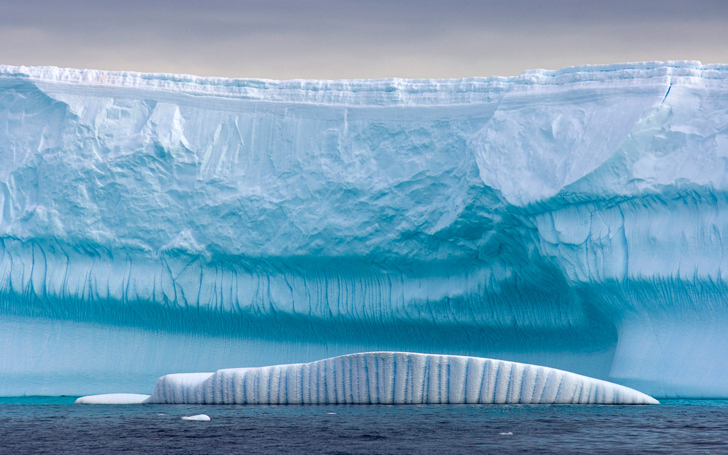 Caption:ANTARCTICA - UNDATED:***EXCLUSIVE*** An iceberg in front of a glacier, on the Western Antarctic peninsula, Antarctica, Southern Ocean. Humans may have spent thousands of year perfecting art and architecture but these incredible photographs of spectacular icebergs show they are no match for nature's grand designs. Captured off the Western Antarctic peninsula the colossal ice carvings have been whittled away by biting polar winds, water, and chilling sub-zero temperatures to form incredible mega structures that take the breath away. In the vast array of jaw-dropping shapes some icebergs feature towering pillars of ice while others appear to have had bridges and tunnels masterfully bored into their huge floating masses. Some even take on the form of gigantic frosty bridges of ice and snow with intricate 'arches' carved out by the harsh Antarctic conditions. Photogrpaher Steven Kazlowski, 40, witnessed the amazing sights as he toured the world's most southerly continent on a 62-foot engined sailing boat. Against the jaw-dropping Antarctic background each paints a magnificent picture - and even caught the eyes of passing Gentoo penguins and humpback whales. (Photo by Steven Kazlowski / Barcroft Media / Getty Images)