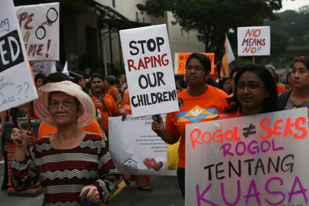 KUALA LUMPUR, MALAYSIA - JUNE 07: Members of All Women's Action Society (AWAM), a Malaysia non-government organisation, hold placards during a peaceful public protest titled 'Citizens Against Rape Walk', demanding better protection for women and girls against sexual violence, on June 7, 2015 in Kuala Lumpur, Malaysia. Malaysian parliament reported that the conviction rate for sexual crimes involving children in 2013 was below 5% and that more than 65 percent of all sexual assault victims between 2012 and 2013 were under 18 years of age. AWAM members wore orange to signify the bright future that Malaysian's hope for their children and carried toys and flowers to signify childhood innocence to which all children have the right. (Photo by Mohd Samsul Mohd Said/Getty Images)