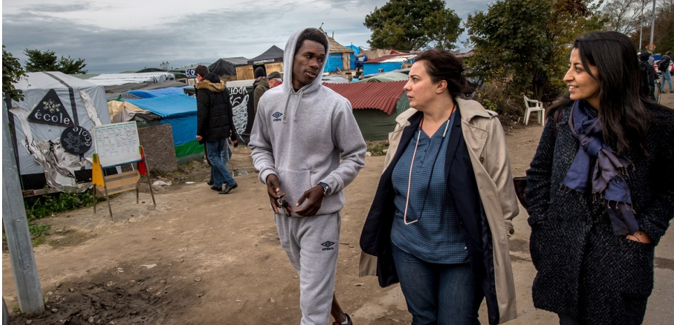 "Europe Ecology - The Greens (EELV) National Secretary Emmanuelle Cosse (C) and EELV European MP Karima Delli (R) speak to a resident as they visit the ""Jungle"", a migrant and refugee camp, in Calais on October 30, 2015.<div class="