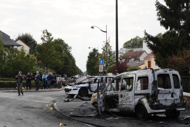 "People gather near a burned police vehicle and a van in Viry-Chatillon on October 8, 2016 after police in their patrol car were attacked by individuals who launched Molotov cocktails, leaving two officers injured. Two officers were ""seriously injured"" when ten individuals launched Molotov cocktails at their vehicle, according to a police source. The officers in their vehicle were responsible for monitoring footage from a camera near a traffic light in Viry-Chatillon. / AFP PHOTO / Thomas SAMSONTHOMAS SAMSON/AFP/Getty Images"