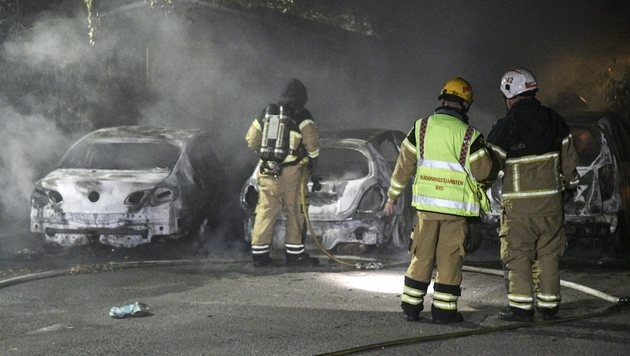epa05489152 Swedish firemen stand next to extinguished car that were set on fire, in Malmo, Sweden, close to midnight on 15 August 2016. Media reports state that Swedish police is investigating a series of vehicle burnings in various Malmo neighborhoods but was so far unable to get hold of any perpetrators. EPA/JOHAN NILSSON SWEDEN OUT