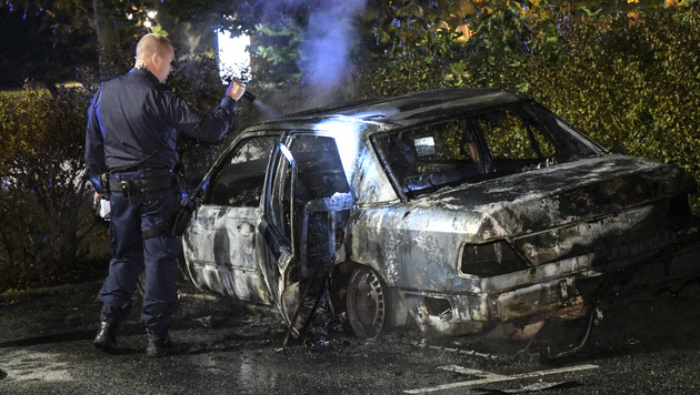 A police officer checks a burned out car at Karleksvagen in Burlov, near Malmo, Sweden, Tuesday Sept. 20, 2016. Police in Malmo say a recent surge in car fires, with about 30 cars set ablaze since Friday, could be linked to a crackdown on gangland crime, after police arrested three men with suspected links to organised crime involving guns and explosives. (Johan Nilsson / TT via AP)