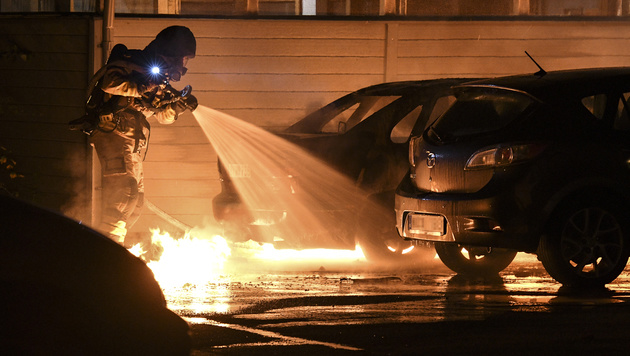 A firefighter works to extinguish a car fire at Persborgsgatan in Malmo, Sweden, Tuesday Sept. 20, 2016. Police in Malmo say a recent surge in car fires, with about 30 cars set ablaze since Friday, could be linked to a crackdown on gangland crime, after police arrested three men with suspected links to organised crime involving guns and explosives. (Johan Nilsson / TT via AP)